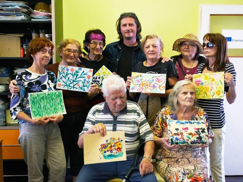 Na fotografii sú účastníci výtvarnej skupiny svetlo, ktorí v rukách držia svoje diela.