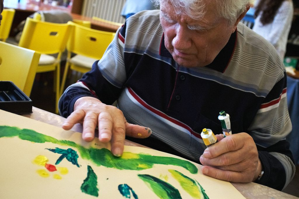 Na fotografii je starší pán, ktorý prstami maľuje temperovými farbami jarnú lúku