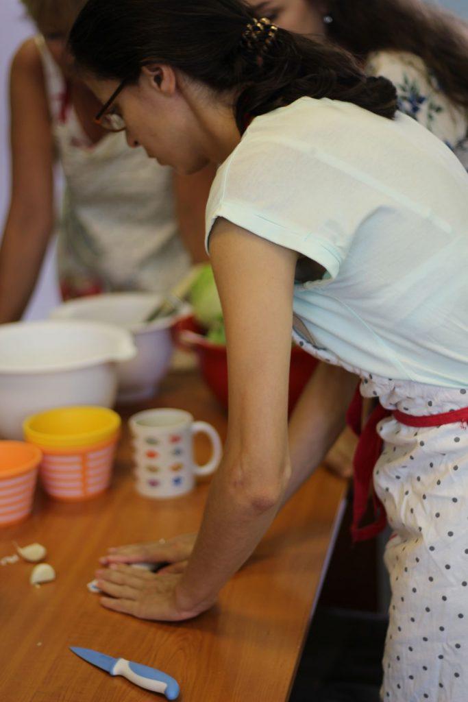 Účastníčka kurzu čistí cesnak