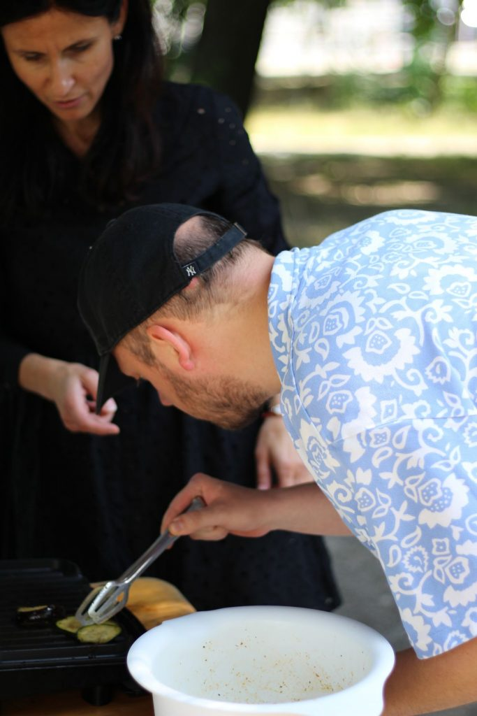 Účastník kurzu kontroluje cuketu na grile pod dohladom inštruktorky sociálnej rehabilitácie