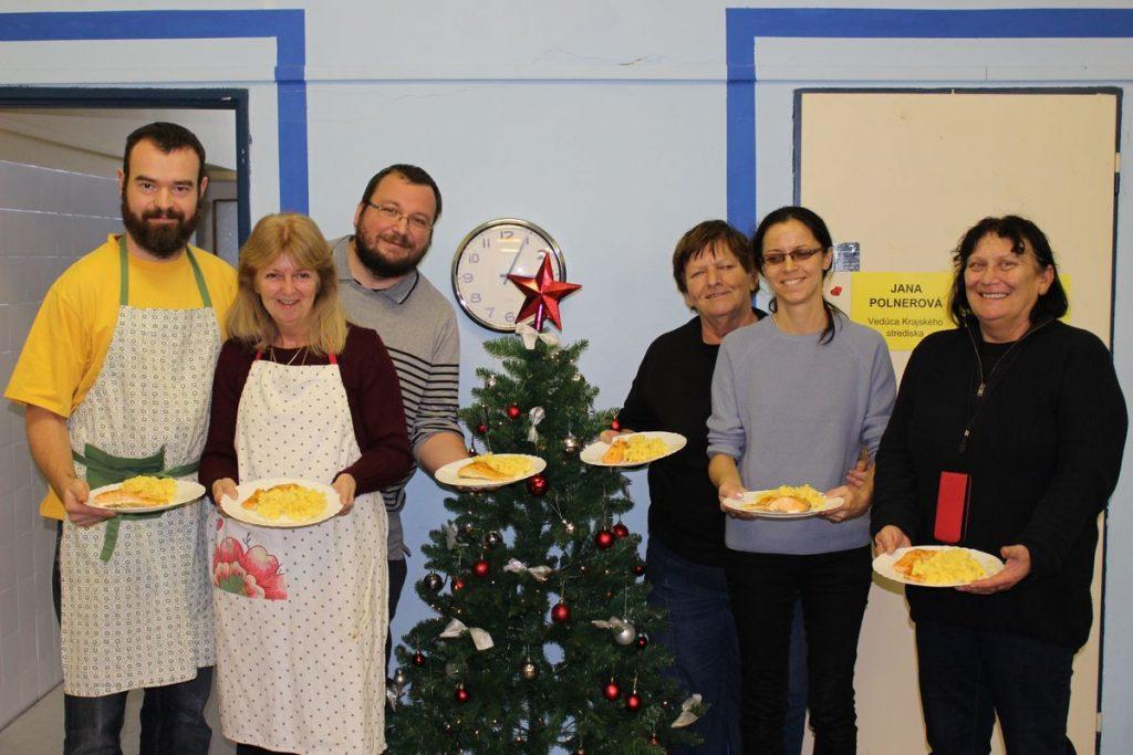 Na spoločnej fotografii účastníci kurzu spolu s kuchárom Martinom a inštruktorom sociálnej rehabilitácie Tomášom pózujú s taniermi navareného jedla pri vianočnom stromčeku