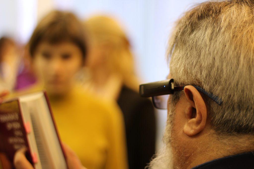 Na fotografii predvádza pán Maj čítačku OrCam pripevnenú na okuliarovom ráme ako číta z knihy.