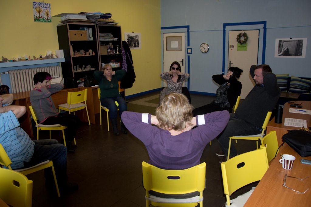 Účastníci tréningu pamäti sedia v kruhu pri rozcvičke.