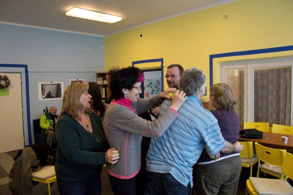 Účastníci tréningu pamati stoja v kruhu a navzájom sa masírujú loptičkami.