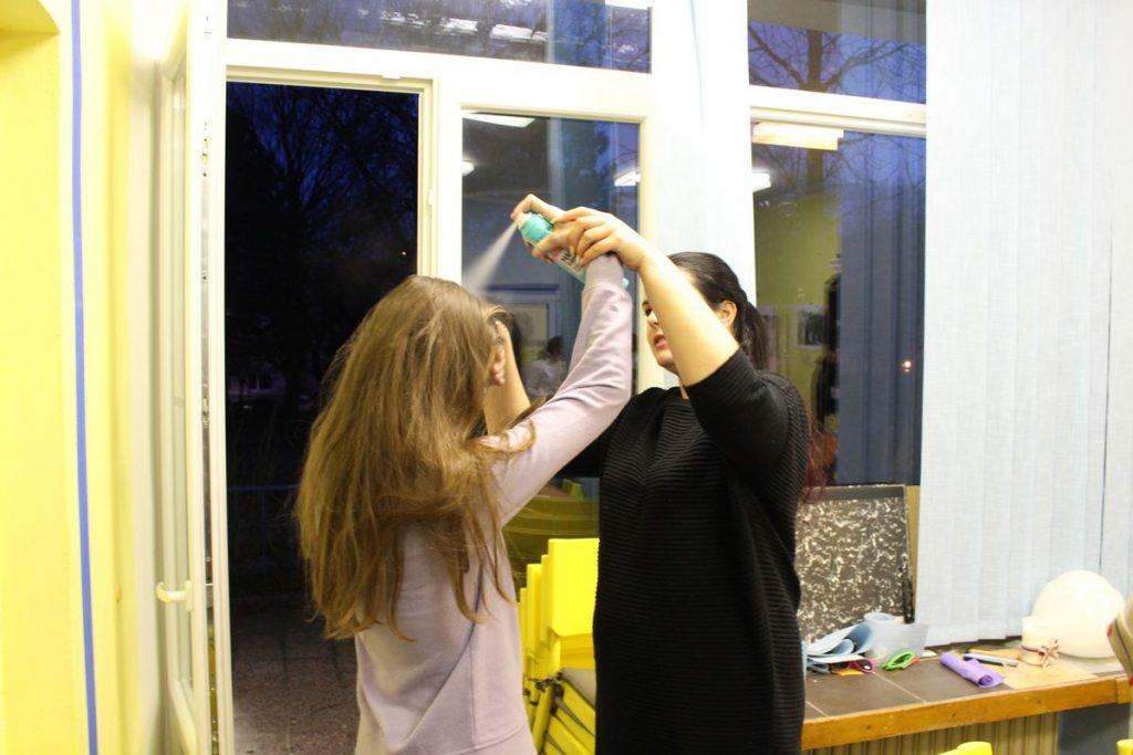 Na fotografii inštruktorka učí, ako správne použiť suchý šampón. Klientke drží ruku v dostatočnej vzdialenosti od vlasov.
